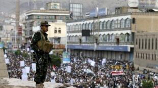 Mpiganaji wa waasi wa Kishia wa Huthi akitoa ulinzi, wakati ambapo raia wa Yemen wakiendelea kuandamana dhidi ya mashambulizi ya Saudi Arabia, Sanaa, Julai 24 mwaka 2015.