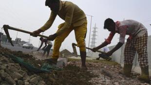 Unos trabajadores cavan la tierra con unas azadas durante las obras de construcción de una línea de ferrocarril en India, el 15 de septiembre de 2020 en Ghaziabad, cerca de Nueva Delhi