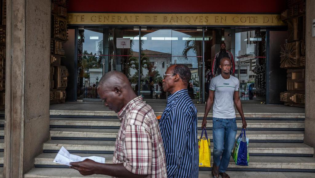 Des passants en face de l'entrée de la Société Générale de Banques à Abidjan en Côte d'Ivoire. (Image d'illustration)