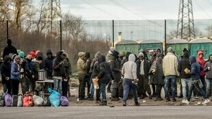 Migrants queue during a food distribution by an association helping migrants in Calais, on February 2, 2018, a day after a giant brawl between Afghans and Eritreans migrants left four of them fighting for their lives.
