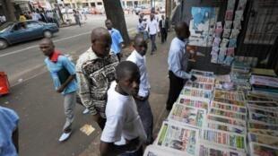 Des hommes devant un étalage de journaux, dans les rues d'Abidjan.