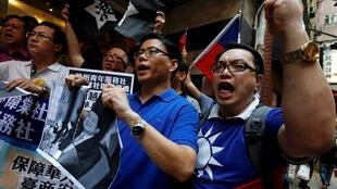 """Members from a pro-Taiwan group """"China Youth Service & Recreation Centre"""" tear a portrait of Vietnamese President Truong Tan Sang as they chant slogans, demanding apology and compensation from Vietnam, outside the Vietnamese Consulate in Hong Kong May 15,"""