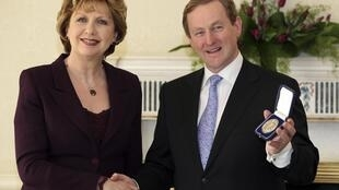Ireland's President McAleese (L) presents newly elected prime minister Enda Kenny with his seal of office