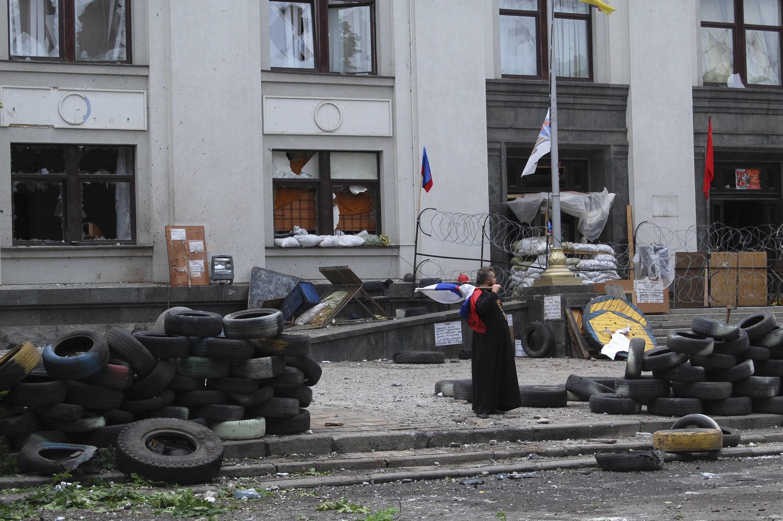 Padre segura uma bandeira russa diante do prédio da administração local de Lugansk, ocupado por separatistas