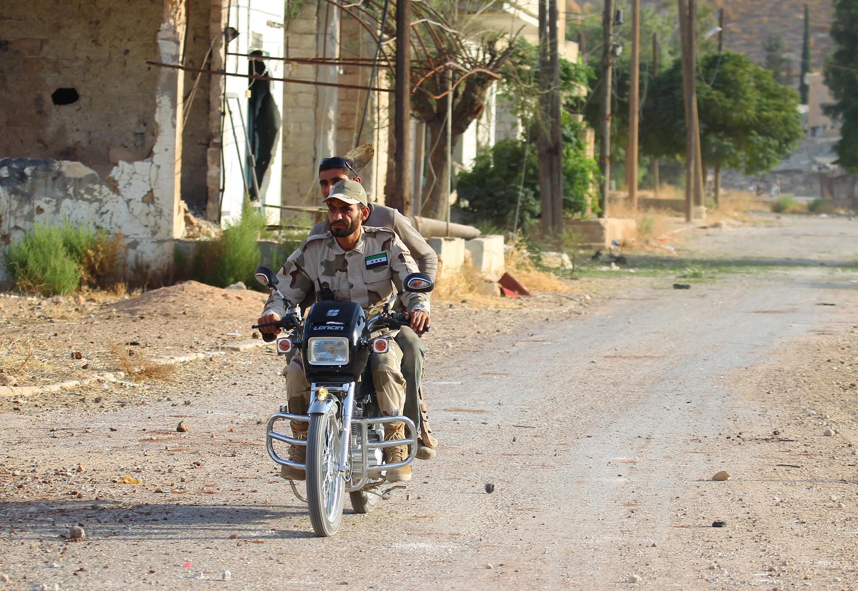 Hai chiến binh nhóm Tajammu al-Izza, thuộc phe nổi dậy Quân đội Syria Tự do, tại Latamneh, phía bắc Hama, nơi vừa bị không quân Nga tấn công. Ảnh chụp ngày 02/10/2015.