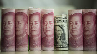 Cette photo prise le 6 janvier 2017 montre des billets de 100 yuans chinois et un billet de dollar américain à Beijing.