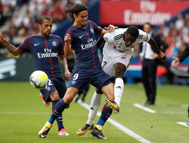 O brasileiro Daniel Alves (esquerda) e o uruguaio Edinson Cavani (centro) deram a vitória ao PSG por 2-0 frente ao Amiens do francês Harisson Manzala, no Parque dos Príncipes na capital gaulesa.