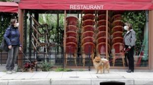 4月22日,在法國南部的尼斯,在一家停業的餐館前,兩位遛狗的行人,戴着口罩,在聊天。