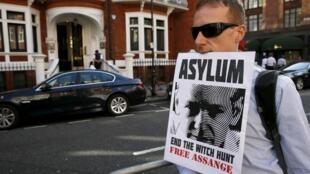 Homem protesta em frente a embaixada do Equador em Londres, onde Julian Assange está refugiado há três anos.