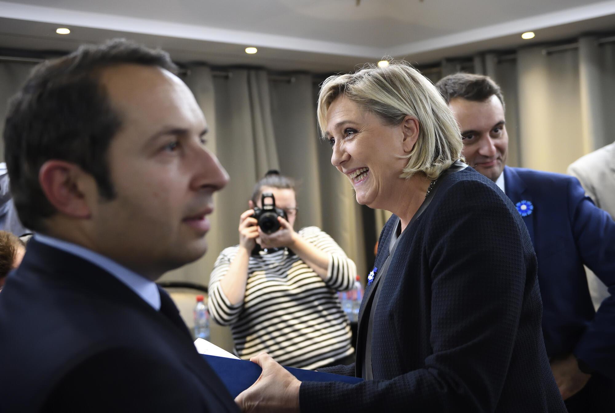 Marine Le Pen, entre Florian Philippot (d) e Sébastien Chenu (e) durante uma convenção do partido Frente Nacional
