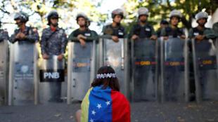 Une manifestante face à la police, lors d'un rassemblement pour dénoncer la mort de l'ex-inspecteur de la police scientifique, le 20 janvier 2018 à Caracas.