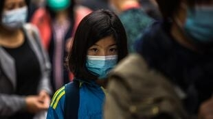 People wearing protective face masks walk along a street in Hong Kong on February 9, 2020, as a preventative measure after a coronavirus outbreak which began in the Chinese city of Wuhan.