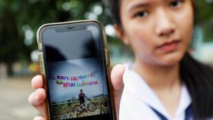 Une étudiante montre la photo de l'un de ses camarades qui fait partie du groupe d'adolescents bloqués dans la grotte de Tham Luang, le 2 juillet 2018.