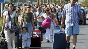 Turistas chegam a pé ao aeroporto de Herakleion, na ilha de Creta, que teve os acessos bloqueados pelos taxistas grevistas na segunda-feira, 01/08/ 2011.