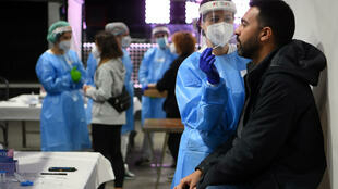 A health worker collects a swab sample from a man in Barcelona