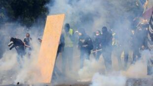 Polícia joga bombas de gás lacrimogêneo nos manifestantes durante a passeata do 1° de maio