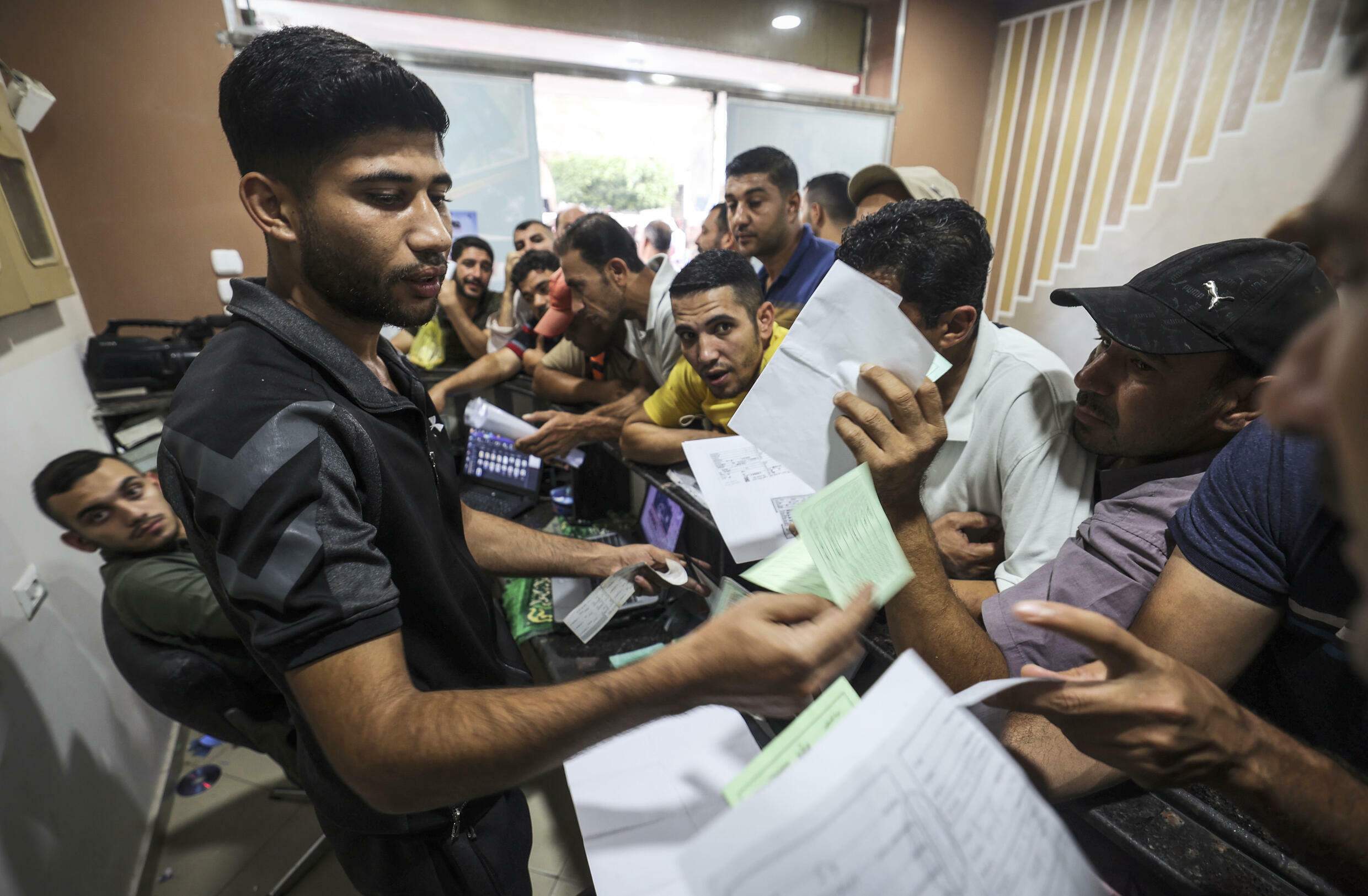 Palestinian men gather to apply for work permits in Israel, at Jabalia refugee camp in the northern Gaza Strip