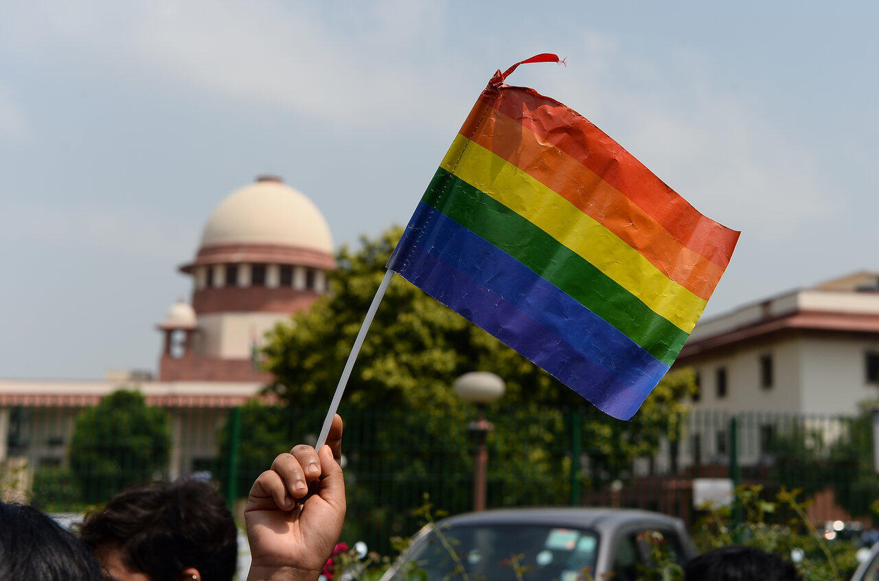 """An Indian member of the lesbian, gay, bisexual, transgender (LGBT) community waves a flag outside the Supreme Court building as crowds gathered to celebrate the decision to strike down the colonial-era ban on gay sex in New Delhi on September 6, 2018. India's Supreme Court on September 6 struck down the ban that has been at the centre of years of legal battles. \\\""""The law had become a weapon for harassment for the LGBT community,\\\"""" Chief Justice Dipak Misra said as he announced the landmark verdict.<br><br>SAJJAD HUSSAIN / AFP"""