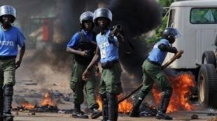 La police guinéenne dégage une barricade en feu, dans une rue de la capitale Conakry, le 15 novembre 2010.