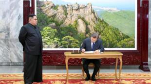 Le président sud-coréen Moon Jae-in, signant un registre sous les yeux du numéro un nord-coréen Kim Jong-un, le 26 mai 2018 à Panmunjeom.