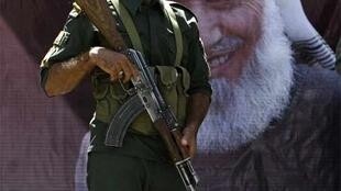 An Afgahn soldier in front of a poster of Burhanuddin Rabbani outside his house Wednesday