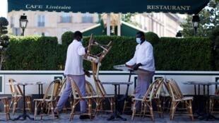 Deux employés du café restaurant Les Deux Magots à Paris préparent la terrasse de l'établissement pour accueillir ses futurs clients.