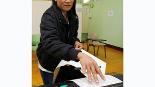 A Filipina voting early in Hong Kong uses the electronic system