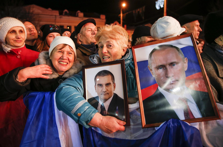 Des femmes brandissent les portraits de Sergei Aksyonov, chef du gouvernement de Crimée, et de Vladimir Poutine, lors d'un concert organisé à Simferopol, pour marquer le premier anniversaire du rattachement de la péninsule à la Russie, le 16 mars 2015.