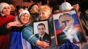 Mulheres com os retratos do chefe do governo da Crimeia e do presidente russo, a 16 de Março durante um concerto comemorativo