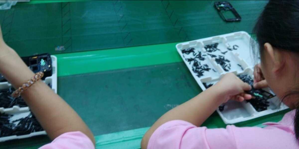Trẻ em trong công tác lắp ráp điện thoại di động Samsung.