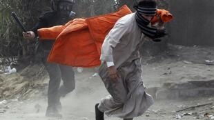Polícia egípcia persegue manifestante que participava de protestos contra o presidente Mohamed Mursi no Cairo.