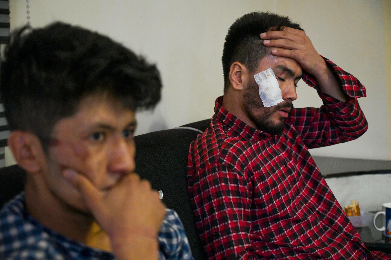 Los periodistas afganos del diario Etilaat Roz  Taqi Daryabi (I) y Nematullah Naqdi (D) en su oficina de Kabul tras haber sido liberados por los talibanes, el 8 de septiembre de 2021