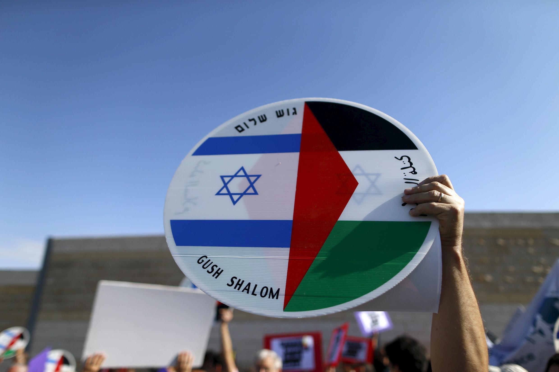 Израильский и палестинский флаги на щите активиста во время манифестации за благополучное будущее израильтян и палестинцев,  Вифлеем, 5 февраля 2016.