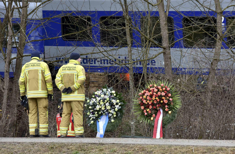 Membros da equipe de resgaste observam coroas de flores colocadas em homenagem às vítimas do acidente de trem na Baviera.