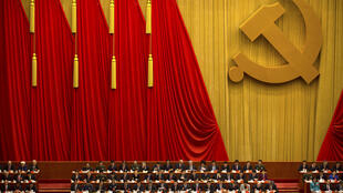 "Attendees read a work report during the opening session of China's 19th Party Congress at the Great Hall of the People in Beijing, Wednesday, Oct. 18, 2017. Chinese President Xi Jinping on Wednesday urged a reinvigorated Communist Party to take on a more forceful role in society and economic development to better address ""grim"" challenges facing the country as he opened a twice-a-decade national congress."