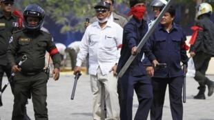 Des agents de sécurité et des hommes en civils armés de bâtons et de barres ont délogé les opposants de la place de la Liberté et quadrillent les rues de Phnom Penh, le 4 janvier 2014.