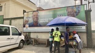 IMAGE Des Ivoriens à Abidjan devant une affiche de la Commission électorale (CEI) à la veille des élections législatives, le 5 mars 2021.