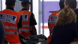 Policiais argentinos carregam corpo retirado do local onde ocorreu o acidente de trem que matou 50 pessoas, em Buenos Aires.