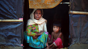 Rohingya refugees sit at the entrance to their shelter in Palong Khali refugee camp near Cox's Bazar in Bangladesh.