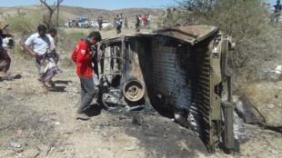 Pessoas observam carro atingido por drone no sábado, em ataque que matou 10 supostos membros da Al Qaeda.
