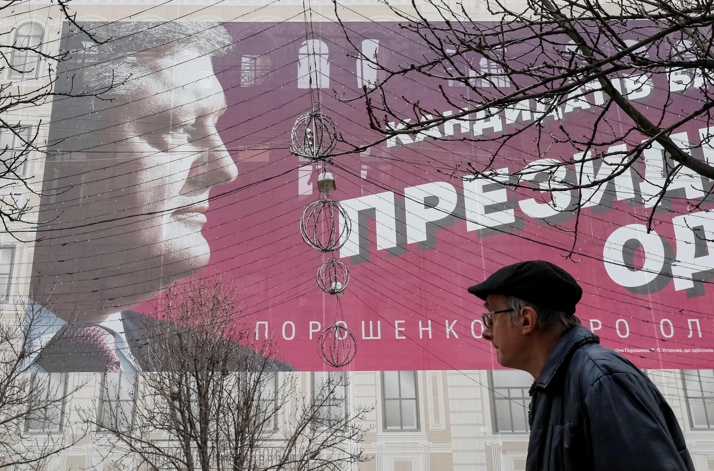 A man passes by a pre-election poster of Ukrainian President and presidential candidate Petro Poroshenko in central Kiev, Ukraine March 25, 2019