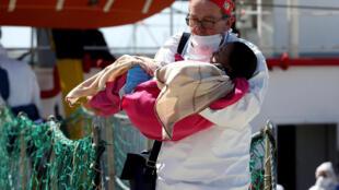 Un médecin de MSF avec un enfant secourus en mer débarque à Pozzallo, en Sicile, en avril 2016.