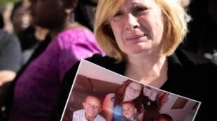 A mãe de Johanna Tilly exibe foto da jovem com os três filhos, diante dos quais foi morta a facadas pelo marido, na última segunda-feira (16).