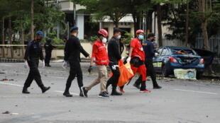 Сотрудники Красного Креста Индонезии несут сумку с телом после взрыва возле католической церкви в Макасаре. 28.03.2021