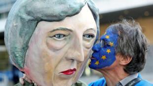 Мужчина целует фигуру, изображающую Терезу Мэй, на акции против Брекзита перед зданием Еврокомиссии в Брюсселе, 21 марта 2019.