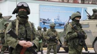 Des hommes armées près de véhicules de l'armée russe, dans la ville ukrainienne de Balaclava, en Crimée, le 1er mars 2014.