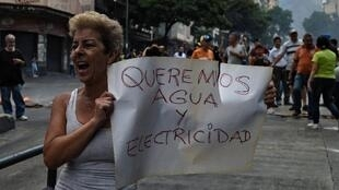 """Milhões de venezuelanos ficaram sem uma gota de água em um cenário de desabastecimento provocado pela série de apagões.dade"""" diz pancarta durante protesto em Caracas, Venezuela."""