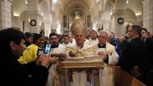 Patriarca de Jerusalém, Fouad Twal, carrega uma estatueta do Menino Jesus durante a celebração de Natal na Igreja da Natividade em Belém, neste 25 de dezembro de 2014.