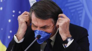 Esta imagen, tomada el 20 de marzo de 2020 en Brasilia, muestra al presidente de Brasil, Jair Bolsonaro, con una máscara de protección durante una conferencia de prensa en el Palacio de Planalto sobre la pandemia del nuevo coronavirus