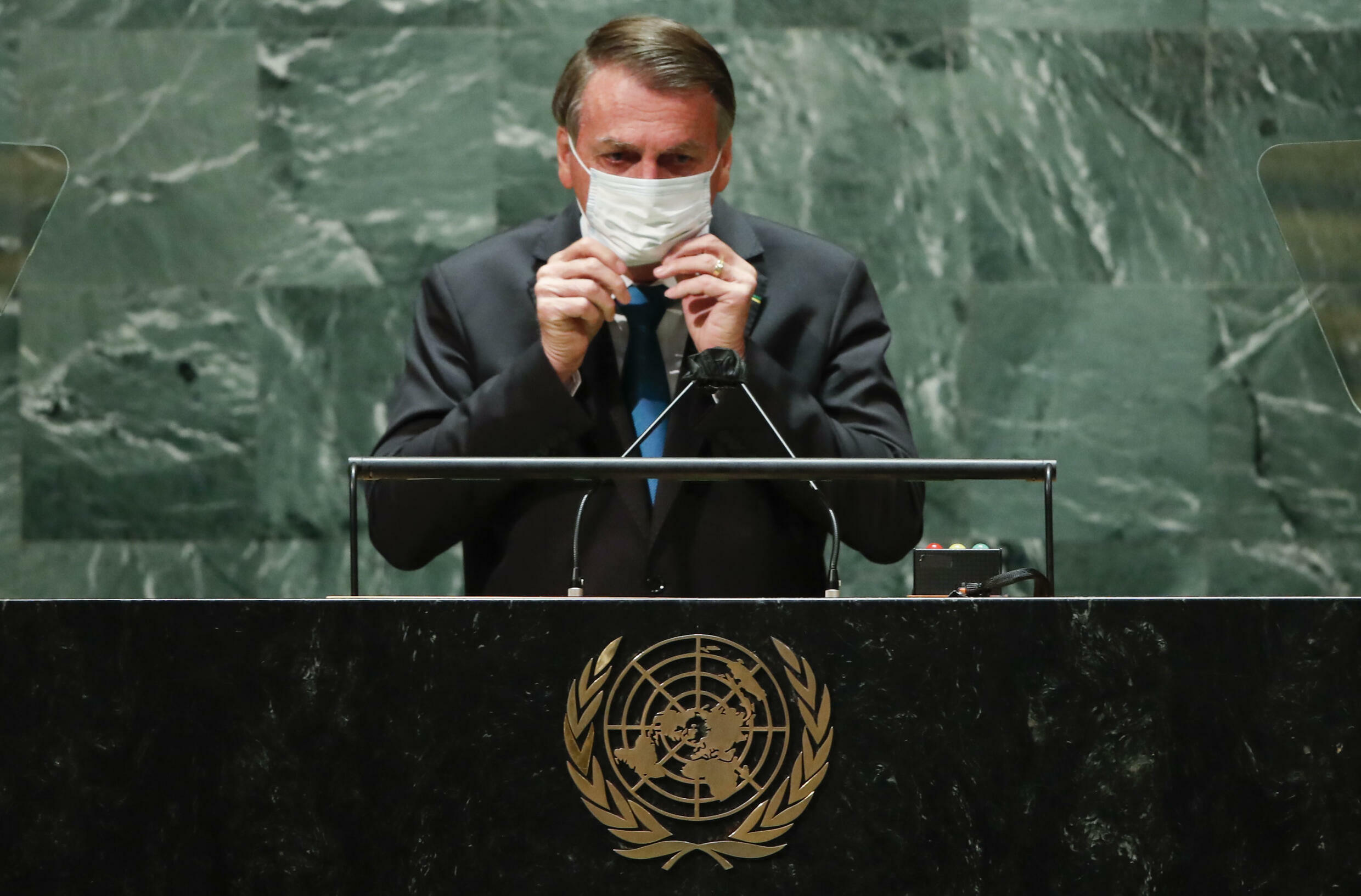 Brazil's President Jair Bolsonaro puts facemask back on after addressing the UN General Assembly on September 21, 2021